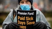 Man with Paid Sick Days Sign